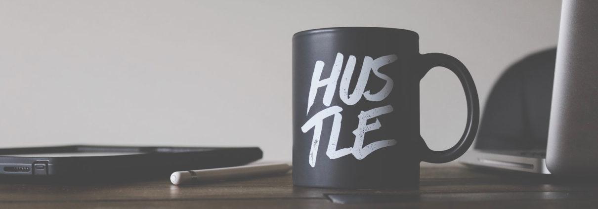 A mug on a desk with hustle written on it.